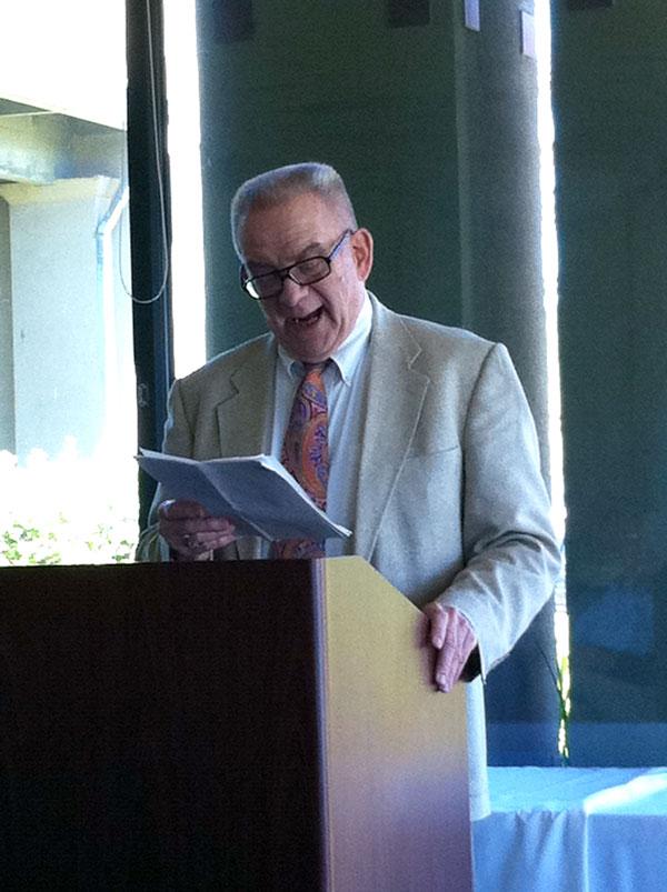 man at podium reading a speech